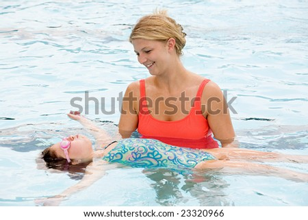 Mother Helping Daughter To Float on Her Back - stock photo