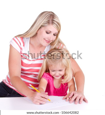 Mother helping daughter write alphabet, sitting at a desk - stock photo