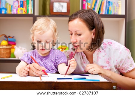 Mother helping her daughter to draw - stock photo