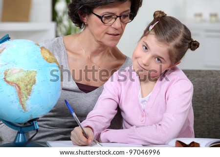 Mother helping her daughter with her homework. - stock photo