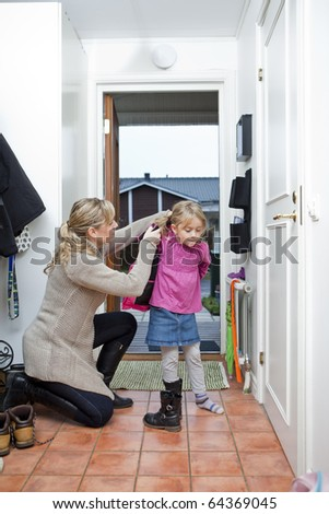 Mother helping her daughter with the jacket