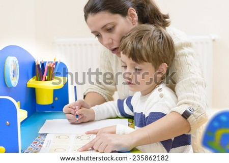 Mother helping her kid to make drawings - stock photo