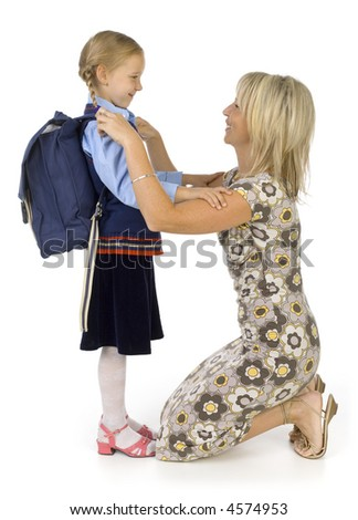 Mother helping her's young daughter prepare to school. Isolated on white in studio. Side view, whole body - stock photo