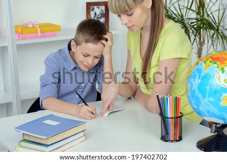 Mother helping to her son doing homework at home - stock photo