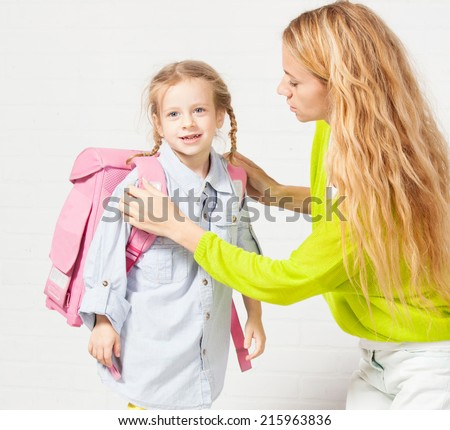 Mother helps her daughter get ready for school. Mom support child to wear a backpack - stock photo