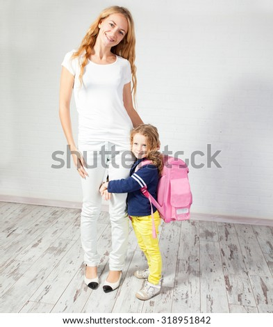 Mother helps her daughter get ready for school. Mom with child - stock photo