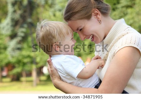 Mother hold baby on hands outdoor in summer and looks on each other - stock photo