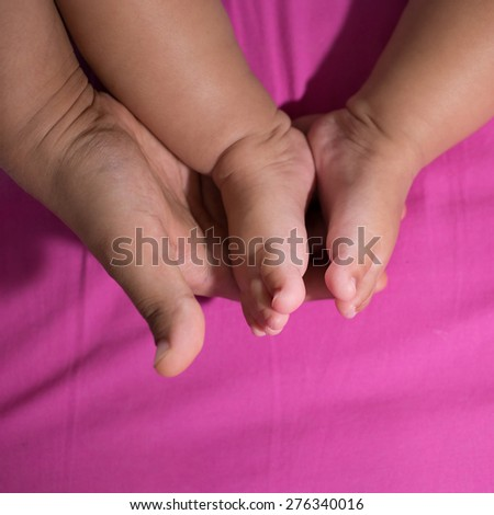 mother hold feets of cute newborn baby - stock photo