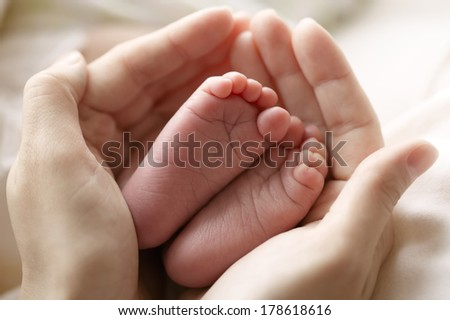 mother hold feets of newborn baby