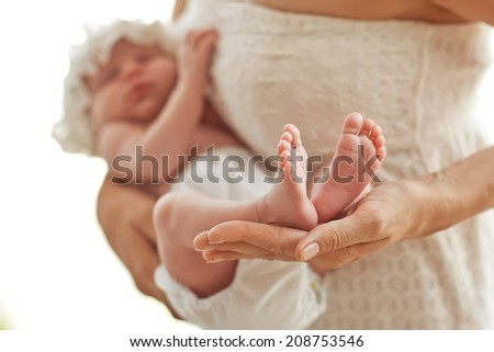 mother hold feets of newborn baby - stock photo