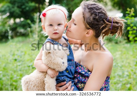 Mother hold her child on hands. Outdoor portrait - stock photo