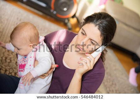 Mother holding a baby girl while talking on a phone.