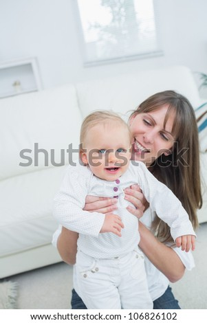 Mother holding a baby in living room