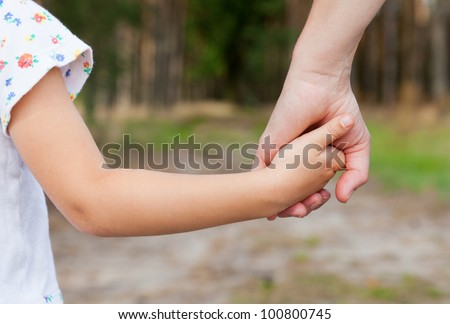 Mother holding a hand of her daughter  in spring day outdoors