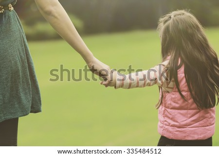 Mother holding a hand of her daughter in summer day outdoors - stock photo
