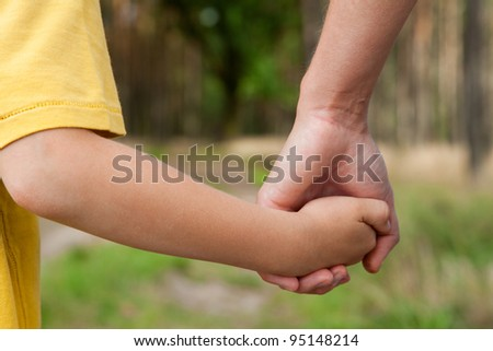 Mother holding a hand of his son in spring day outdoors - stock photo