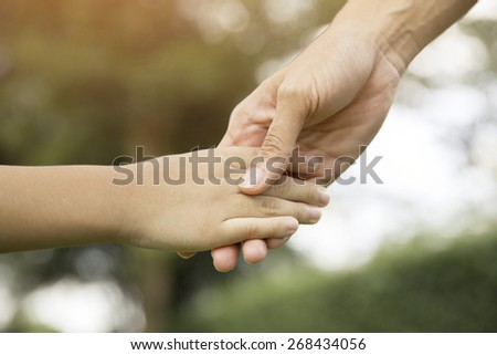 Mother holding a hand of his son in summer day - stock photo