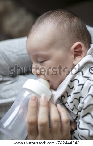 Mother holding and feeding newborn baby from bottle.