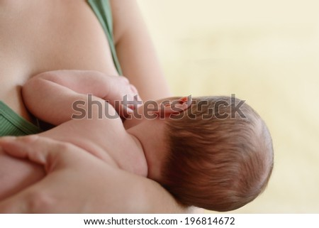 Mother holding and feeding newborn baby soft focus on the ear - stock photo