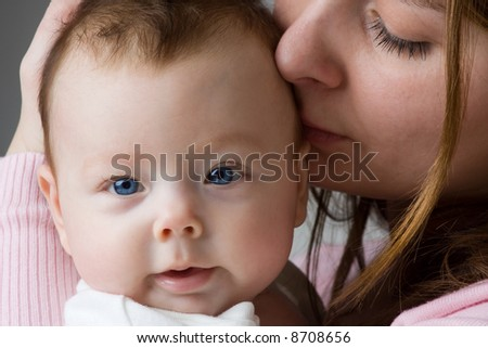 Mother holding baby and kissing her head - stock photo