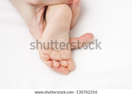 mother holding baby foot