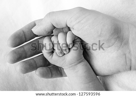 Mother holding baby hand - stock photo