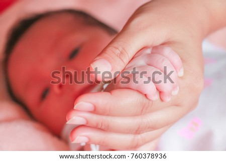 Mother holding baby infant little hand