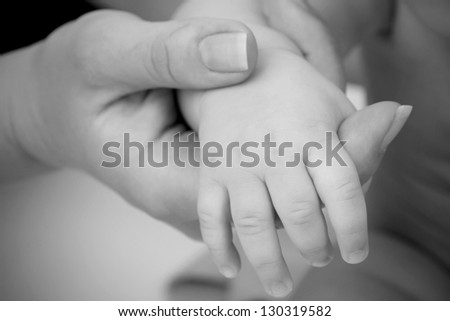 mother holding baby's hand closeup, black and white