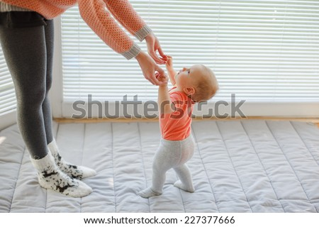 mother holding baby's hands to help him/her to walk over white background, windows - stock photo