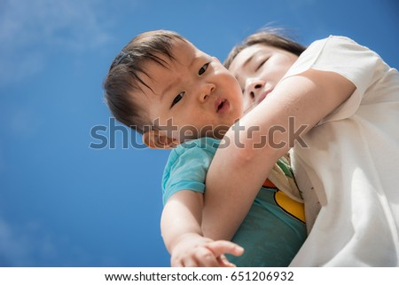 mother holding baby sky background
