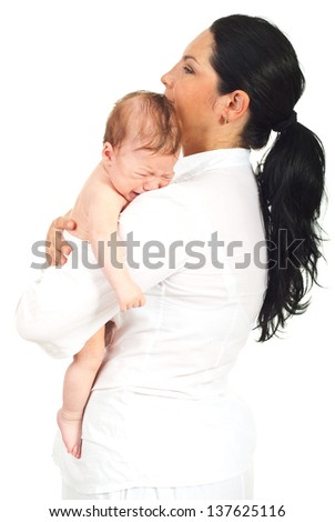 Mother holding crying newborn on her shoulder and standing in profile isolated on white background