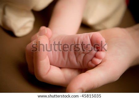 Mother holding foot of her newborn baby