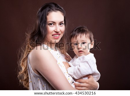 Mother holding her baby child in hands in studio photo on brown background