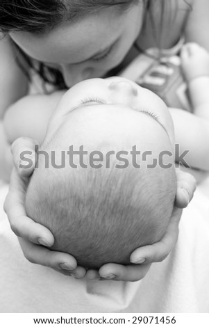 Mother holding her child's head, shallow focus - stock photo