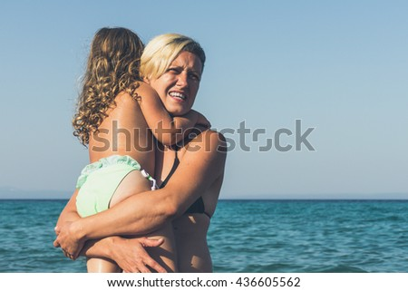Mother holding her daughter against blue sky and sunshine - stock photo