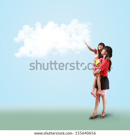 Mother holding her little daughter and catch something on the cloud, Useful for background - stock photo