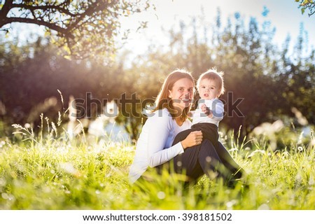 Mother holding her little son, sitting on the grass