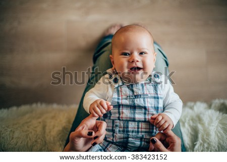 Mother holding her smiling newborn son in hands - stock photo