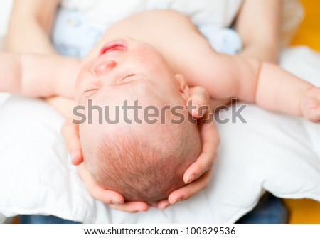 Mother holding little baby girl crying - stock photo