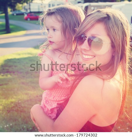 Mother holding little girl in arms - instagram effect - stock photo