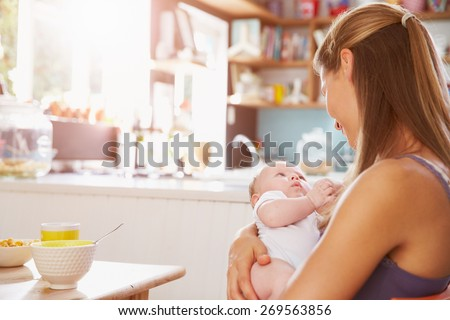 Mother Holding Newborn Baby Daughter At Kitchen Table - stock photo