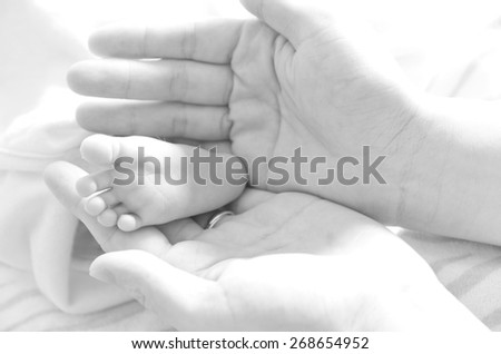Mother holding newborn baby's foot - stock photo