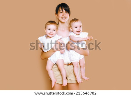 Mother holding on the hands twins baby - stock photo