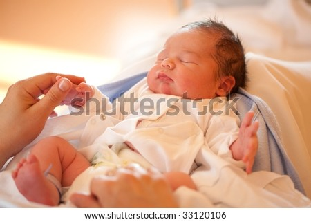 Mother holding she's new born baby's hand - stock photo