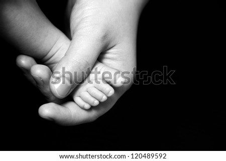 Mother holding tiny foot of newborn baby - stock photo