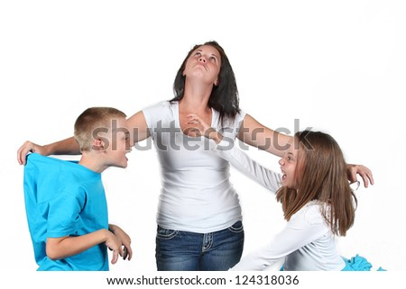 Mother holding two kids as they fight with each other. - stock photo