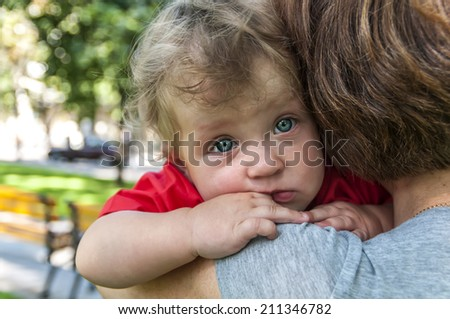 mother holds a sad child - stock photo