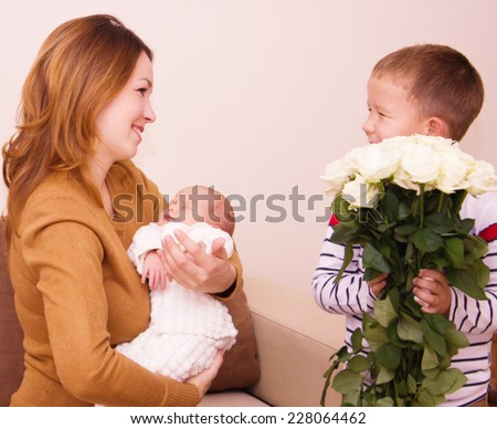 Mother holds cute baby, gift flowers for my mom - stock photo