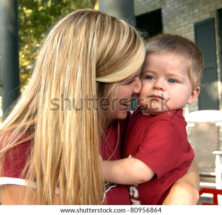 Mother holds her baby and squeezing him lovingly.  Her face is next to his and her arms are hugging him. - stock photo