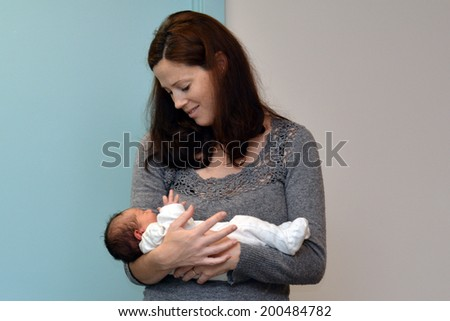 Mother holds her newborn ( 2 days old) baby. - stock photo